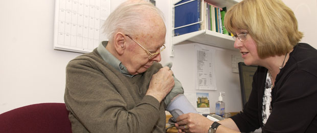 This image taken in a GP surgery in King Edwards Road, London, shows a female GP consulting with an elderly patient.